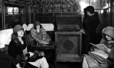 Women in hats and fur coats listen to gramophone record in train carriage